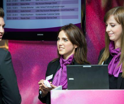 Zwei stewards Empfangs-Mitarbeiterinnen stehen hinter dem Laptop beim Check-in eines Events.