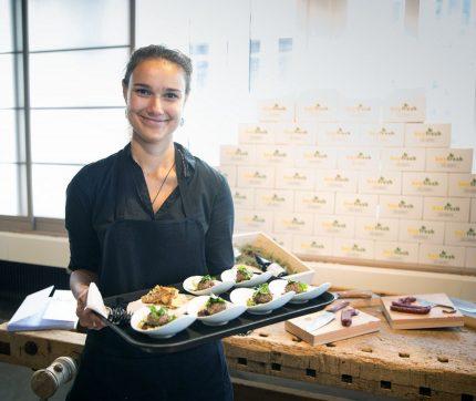 Eine stewards Serviceangestellte hält ein Serviertablett mit Gerichten und lächelt in die Kamera.