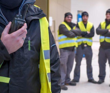 Vier Security & Safety Mitarbeiter von stewards stehen im Halbkreis, wobei der eine ein Funkgerät hält.