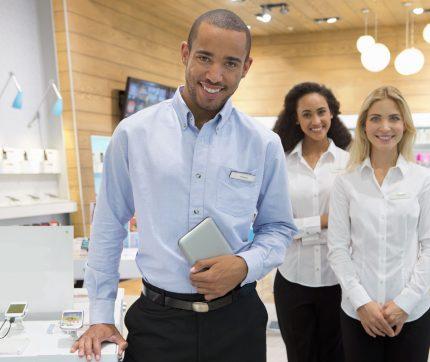 Drei Sales Mitarbeitende von stewards in einem Mobiltelefongeschäft