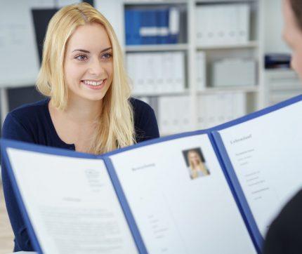 Eine junge Frau sitzt in einem Büro gegenüber einem Mann, der ihren Lebenslauf anschaut.